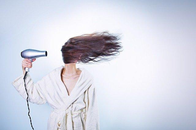 femme en peignoir avec sèche cheveux dans la main